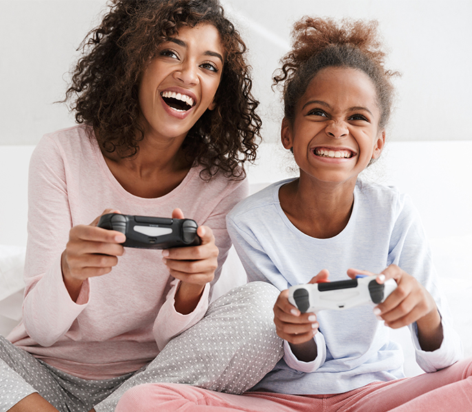 Mother and daughter gaming in their living room with Spectrum Internet